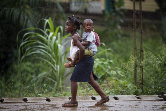 A girl carries a child as they walk back from school during a rain shower in Bata, Equatorial Guinea, Monday, Feb. 6, 2012. An outbreak of the deadly Ebola virus is believed to have killed at least 59 people in Guinea and may already have spread to neighboring Liberia, health officials said Monday. (AP Photo/Ariel Schalit)