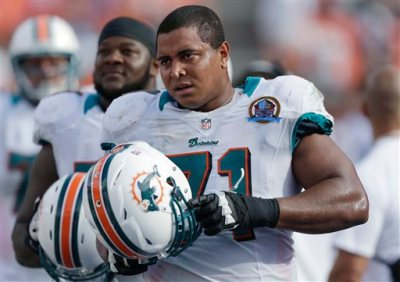 In this Dec. 16, 2012, photo, Miami Dolphins tackle Jonathan Martin (71) stands on the sidelines during the Dolphins' NFL football game against the Jacksonville Jaguars in Miami. Martin, the offensive tackle at the center of the Dolphins' bullying scandal, has been traded to the San Francisco 49ers. The Dolphins announced the deal Tuesday night, March 11, 2014, on the first day of NFL free agency. Martin's move cross country brings him back to the Bay Area to be reunited with his former Stanford coach, Jim Harbaugh. (AP Photo/Wilfredo Lee)