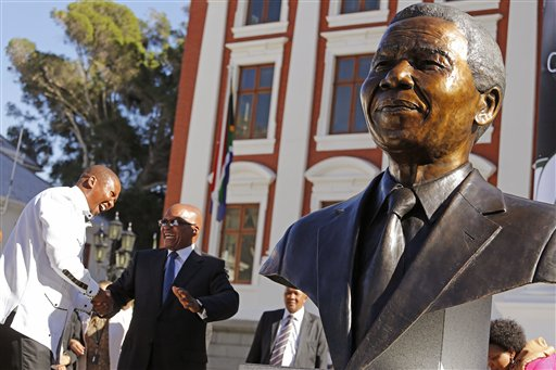South African President Jacob Zuma, second left, talks with Mandla Mandela, left, after they and other dignitaries unveiled a bust of former South African President Nelson Mandela, right, at the South African Parliament in Cape Town, South Africa, Monday, April 28, 2014. South African President Jacob Zuma and members of the South African Parliament unveiled the bust of Mandela at Parliament, forming part of celebrations for 20-years anniversary of a democratic Parliament in South Africa after the end of white rule. (AP Photo/Schalk van Zuydam)
