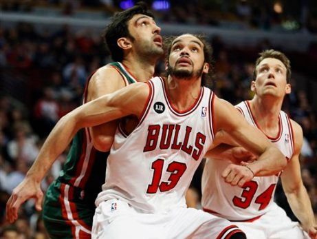 In this April 4, 2014 file photo, Chicago Bulls center Joakim Noah (13) defends against Milwaukee Bucks center Zaza Pachulia during an NBA basketball game in Chicago.  A person familiar with the situation says that Noah is the NBA's Defensive Player of the Year. The person spoke Monday, April 21, 2014 on the condition of anonymity because the award had not been announced. (AP Photo/Kamil Krzaczynski, File)