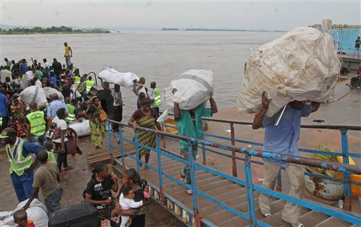 People that have been deported from Congo, arrive by river boat in Kinshasa, Democratic Republic of Congo, Tuesday, April 29, 2014. Officials say nearly 40,000 Congolese citizens have been deported from neighboring Republic of Congo because they did not have immigration papers. Kinshasa Governor Andre Kimbuta said Tuesday that the biggest wave of deportees had arrived the day before, when 6,000 people crossed the Congo River separating the two countries. (AP Photo/John Bompengo)