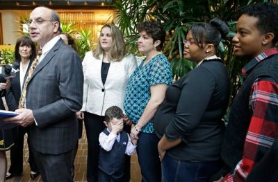 Attorney Al Gerhardstein, left, stands with several same-sex couples at a news conference, Friday, April 4, 2014, in Cincinnati. Civil rights attorneys are arguing in Federal Court on Friday that a federal judge should prohibit Ohio officials from enforcing the state's ban on gay marriage. (AP Photo/Al Behrman)