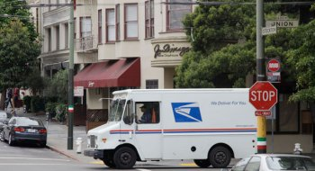US postal service truck drives through the North Beach area of San Francisco. (AP Photo)