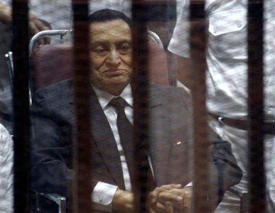 Ousted Egyptian President Hosni Mubarak, sits in the defendants cage behind protective glass, during a court hearing in Cairo, Egypt, Wednesday, May 21, 2014. An Egyptian court has convicted Mubarak of embezzlement and sentenced him to three years in prison. Mubarak's two sons, one-time heir apparent Gamal and wealthy businessman Alaa, were also convicted Wednesday of graft and sentenced to four years in prison each in the same case. (AP Photo/Tarek el-Gabbas)