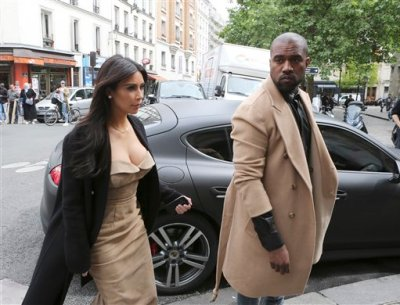 Kim Kardashian and U.S rap singer Kanye West arrive at a luxury shop in Paris, Wednesday, May 21, 2014.  The gates of the Chateau de Versailles, once the digs of Louis XIV, will be thrown open to Kim Kardashian, Kanye West and their guests for a private evening this week ahead of their marriage (AP Photo/Jacques Brinon)