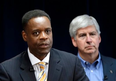 In this March 14, 2013, file photo, Detroit emergency manager Kevyn Orr, left, speaks at a news conference in Detroit as Michigan Gov. Rick Snyder, who appointed Orr, listens. The Koch Brothers' Americans for Prosperity organization is launching an effort to kill the legislative appropriation that is the key to Detroit's bankruptcy settlement. (AP Photo/Paul Sancya, File)