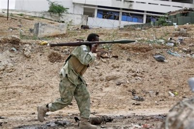 A Somali soldier carrying a rocket launcher runs to fight during an attack on Somalia's parliament in Mogadishu,  Saturday, May 24, 2014.  Militants in Mogadishu carried out a multi-pronged, complex attack against the country's parliament building involving a car bomb, suicide bomber and gunmen on foot, police said. Several people were killed, including six attackers and one soldier who tried to stopped a suicide bomber from entering the building, said police Capt. Mohamed Hussein. (AP Photo/Farah Abdi Warsameh)