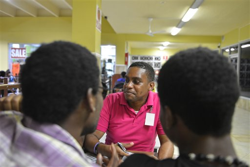 In this, April 25, 2014, photo, gay rights activist James Burton, center, of the Color Pink Group, chats with a group of young homosexual men about HIV and health issues at a shopping mall in Kingston, Jamaica. Gay sex and prostitution is illegal in Jamaica, and LGBT people who sell sex face arrest or worse. But this normally wary group is welcoming a recent outreach as a volunteer reaches out to tthem with health advice. (AP Photo/David McFadden)