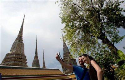 A couple of Western tourists snap a souvenir photo at a Wat Pho temple in Bangkok, Thailand Tuesday, May 27, 2014. The drama of Thailand's military takeover has played out mainly in the political arena. While the army detains political leaders and issues stern warnings on TV, tourists are kicking back on the country's famed beaches and sightseeing in Bangkok. The main impact on visitors for now is a 10 p.m. curfew, which forces nightlife to close four hours earlier. (AP Photo/Sakchai Lalit)