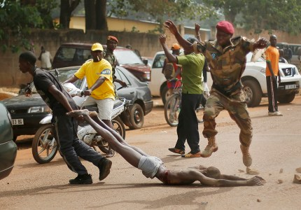 Newly enlisted FACA (Central African Armed Forces) soldiers drag the lifeless body of a suspected Muslim Seleka militiaman moments after Central African Republic Interim President Catherine Samba-Panza addressed the troops in Bangui, Wednesday Feb. 5, 2014. The victim was lynched by hundreds of recruits, pelting him with bricks and mutilating his body with knives. (AP Photo/Jerome Delay)