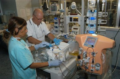 In this image made available by the San Bortolo Hospital in Vicenza on Thursday May 22, 2014 a nurse Mariangela Mettifogo, left, and Dr. Claudio Ronco treat a baby hooked up to a new dialysis machine at the San Bortolo Hospital in Vicenza, Italy, in the  summer of 2013. Doctors in Italy have designed a miniature dialysis machine for babies, used for the first time last year to save a newborn girl, according to a new report.  Usually, doctors adapt standard dialysis machines for babies, but that can be risky since the devices can't always be accurately tweaked. About 1 to 2 percent of hospitalized infants have kidney problems that may require dialysis, which cleans toxins from the blood when the kidneys aren't working. (AP Photo/San Bortolo Hospital )