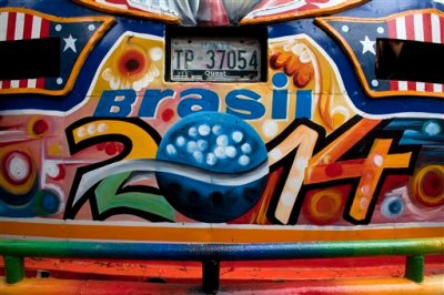 In this May 22, 2014 photo, the Haiti license plate of a tap-tap passenger bus is surrounded by World Cup paintings in Port-au-Prince, Haiti. The brightly painted Haitian minibuses known as tap-taps are getting a bit more colorful in the lead up to the World Cup that starts in June in Brazil. (AP Photo/Dieu Nalio Chery)