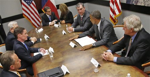 President Barack Obama, center right, meets with Dallas Mayor Mike Rawlings, to the right of the president, and Gov. Rick Perry, top, about border immigrantion during the president's stopover in Dallas on Wednesday, July 9, 2014. (AP Photo/Pool, The Dallas Morning News, Louis DeLuca)