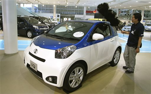 A worker cleans an IQ compact car at a Toyota showroom in Tokyo, Wednesday, July 30, 2014. Toyota remains No. 1 in global vehicles sales after the first six months of this year, followed by Volkswagen which bumped General Motors out of second place as the U.S. automaker grapples with a recall scandal. (AP Photo/Eugene Hoshiko)