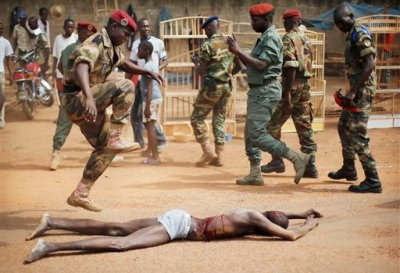 In this file photo taken on Wednesday, Feb. 5, 2014, a FACA (Central African Armed Forces) officer jumps on the lifeless body of a suspected Muslim Seleka militiaman moments after Central African Republic Interim President Catherine Samba-Panza addressed the troops in Bangui, Central African Republic. Amnesty International said Thursday, July 10, 2014 that fighters on both sides of the conflict in Central African Republic are living freely despite committing war crimes and some who have been jailed have escaped from prison. (AP Photo/Jerome Delay, File)