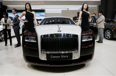 In this Nov. 21, 2013 file photo, models pose beside the Rolls-Royce Canton Glory at the company's booth during Guangzhou 2013 Auto Show in China's southern city of Guangzhou. Britain-based Rolls-Royce on Tuesday, July 8, 2014 said that global sales in the first half of the year were up 33 percent compared with the same period in 2013.  (AP Photo/Kin Cheung, File)