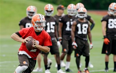 In this June 11, 2014, file photo, Cleveland Browns quarterback Johnny Manziel runs the ball during NFL football minicamp at the team's facility in Berea, Ohio. With LeBron James' return, Johnny Football might not be the top star in Cleveland, but Manziel will still get plenty of attention for what he does on and off the field this summer.  (AP Photo/Mark Duncan, File)