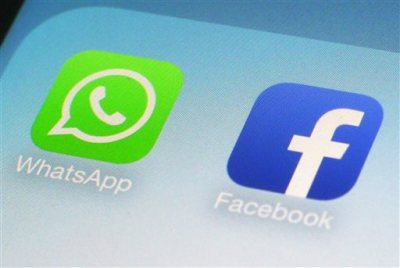 "This Feb. 19, 2014 file photo shows the WhatsApp and Facebook app icons on an iPhone in New York. More ""headline-grabbing"" acquisitions are likely over the coming year as businesses take advantage of a period of improving economic growth and cheap financing, according to business consulting firm EY. Facebook announced its biggest ever acquisition with a proposed $19 billion takeover of WhatsApp. (AP Photo/Patrick Sison, File)"
