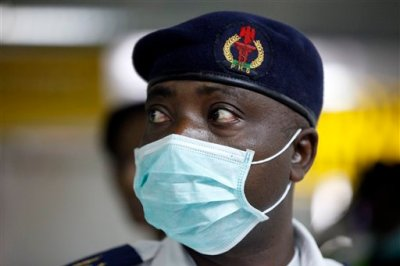 A Nigerian health official wearing a protective mask waits to screen passengers at the arrivals hall of Murtala Muhammed International Airport in Lagos, Nigeria, Monday, Aug. 4, 2014. Nigerian authorities on Monday confirmed a second case of Ebola in Africa's most populous country, an alarming setback as officials across the region battle to stop the spread of a disease that has killed more than 700 people. (AP Photo/Sunday Alamba)