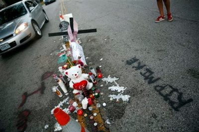 A makeshift memorial sits in the middle of the street where 18-year-old Michael Brown was shot and killed by police, Monday, Aug. 11, 2014, in Ferguson, Mo. The FBI has opened an investigation into the fatal shooting of an unarmed black teenager on Saturday whose death stirred unrest in a St. Louis suburb. (AP Photo/Jeff Roberson)