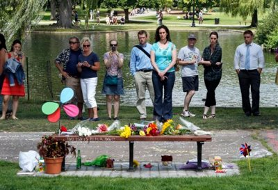 """People pause by a bench at Boston's Public Garden, Tuesday, Aug. 12, 2014, where a small memorial has sprung up at the place where Robin Williams filmed a scene during the movie, """"Good Will Hunting."""" Williams, 63, died at his San Francisco Bay Area home Monday in an apparent suicide. (AP Photo/Elise Amendola)"""