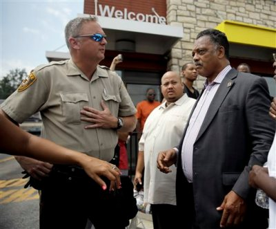 A member of the St. Louis County Police Department asks Rev. Jesse Jackson, right, to move along as they try to keep people from congregating, Monday, Aug. 18, 2014, in Ferguson, Mo. The Aug. 9 shooting of Michael Brown by police has touched off rancorous protests in Ferguson, a St. Louis suburb where police have used riot gear and tear gas. Gov. Jay Nixon ordered the National Guard to help restore order Monday while lifting a midnight-to-5 a.m. curfew that had been in place for two days. (AP Photo/Jeff Roberson)