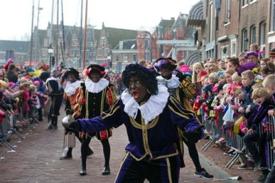 "In this Nov. 16, 2013 file photo a ""Zwarte Piet"" or ""Black Pete"", jokes with children after arriving with Sinterklaas, or Saint Nicholas, by steamboat in Hoorn, north-western Netherlands. Amsterdam's mayor and organizers of a large children's winter festival have unveiled plans on Thursday, Aug. 14, 2014 to reform the image of ""Black Pete"" in order to remove perceived racist elements over a period of years. A large majority of the Netherlands' mostly-white population say Pete is a positive figure and deny any racial insult. But a court and racism experts have found his appearance offensive. (AP Photo/Peter Dejong, File)"