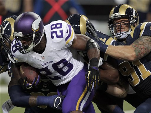 Minnesota Vikings running back Adrian Peterson (28) runs for a 5-yard gain as St. Louis Rams defensive end Chris Long, right, defends during the first quarter an NFL football game Sunday, Sept. 7, 2014, in St. Louis. (AP Photo/Tom Gannam)