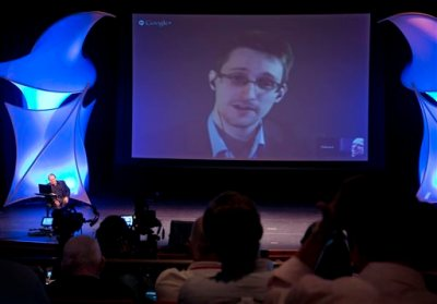 In this June 5, 2014 file photo, former NSA contractor Edward Snowden participates in a conversation via video with John Perry Barlow, co-founder & vice chairman of the Electronic Frontier Foundation, at the 2014 Personal Democracy Forum, at New York University in New York. The boundary between the online and physical worlds got blurry last week when Sony's PlayStation Network was disabled by an online attack, while an American Airlines passenger jet carrying a Sony executive was diverted due to a bomb threat on Twitter. Snowden told Wired magazine early August that the NSA had secretly planned a cyberwarfare program, codenamed MonsterMind, that could automatically fire back at cyberattacks from foreign countries without any human involvement. (AP Photo/Richard Drew, File)