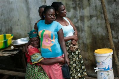 In this photo taken Friday Sept. 26, 2014, Ethel Konneh, left, is consoled by her daughters outside the Island Clinic Ebola isolation and treatment center, after she learned her other daughter Rose Johnson passed away from Ebola in Monrovia, Liberia.  There had been no official confirmation of Rose's death from hospital officials, no time for someone to explain her final moments, just word from a family acquaintance inside who said her bed had been cleared that morning to make way for a new patient. As the death toll from Ebola soars, crowded clinics are turning over beds as quickly as patients are dying. This leaves social workers and psychologists struggling to keep pace and notify families, who must wait outside for fear of contagion. Also, under a government decree, all Ebola victims must be cremated, leaving families in unbearable pain with no chance for goodbye, no body to bury. (AP Photo/Jerome Delay)
