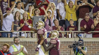 Florida State fans cheer Rashad Greene after a 74-yard touchdown pass in the fourth quarter of an NCAA college football game against Clemson in Tallahassee, Fla., on Sept. 20. In college sports, African-American student athletes and white student audiences are the norm. Commentator Frank Deford asks why this dynamic does not make us more squeamish. (Mark Wallheiser/AP Photo)