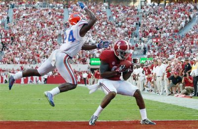 In this Sept. 20, 2014, file photo, Alabama wide receiver Amari Cooper, right, scores a touchdown against Florida defensive back Brian Poole (24) during the second half of an NCAA college football game in Tuscaloosa, Ala. As the season hits the midway point, a Heisman edition of things to watch for this weekend include Cooper. (AP Photo/Brynn Anderson, File)