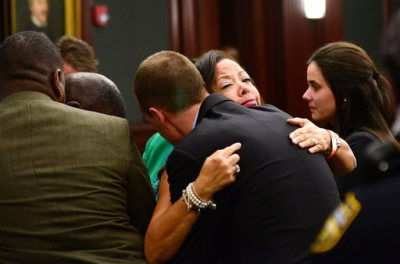 Lucia McBath, mother of Jordan Davis, hugs Det. Mark Musser of the Jacksonville Sheriff's Office, after the verdict in Michael Dunn's retrial, at the Duval County Courthouse in Jacksonville, Fla., Wednesday, Oct. 1, 2014. A jury found Dunn guilty of first-degree murder in his retrial on murder charges for the shooting death of 17-year old Jordan Davis in a dispute over loud music at at Jacksonville gas station in November of 2012. (AP Photo/The Florida Times-Union, Bob Mack, Pool)