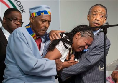 In this July 19, 2014, file photo, Esaw Garner, center, wife of Eric Garner, breaks down in the arms of Rev. Herbert Daughtry and Rev. Al Sharpton, right, during a rally at the National Action Network headquarters for Eric Garner in New York. The city medical examiner ruled that Garner died as a result of a police chokehold during an attempted arrest. Garner's family has filed a notice of claim to sue New York City, the Police Department and six individual police officers for $75 million on Monday, Oct. 6. The notice is the first step toward suing the city over Garner's death on Staten Island in July. A spokesman for city Comptroller Scott Stringer said Tuesday, Oct. 7 the claim is under review. (AP Photo/John Minchillo, File)