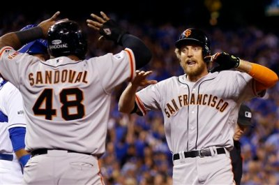 San Francisco Giants' Hunter Pence is congratulated by Pablo Sandoval after Pence hit a two-run home run during the first inning of Game 1 of baseball's World Series against the Kansas City Royals Tuesday, Oct. 21, 2014, in Kansas City, Mo. (AP Photo/David J. Phillip)