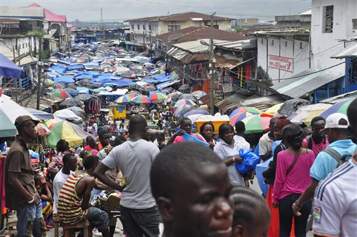 In this Aug. 19, 2014 file photo, people do business at the Waterside local market in the center of Monrovia, Liberia. Just as their economies had begun to recover from the man-made horror of coups and civil war, the West African nations of Guinea, Liberia and Sierra Leone have been knocked back down by the Ebola virus. (AP Photo/Abbas Dulleh, File)