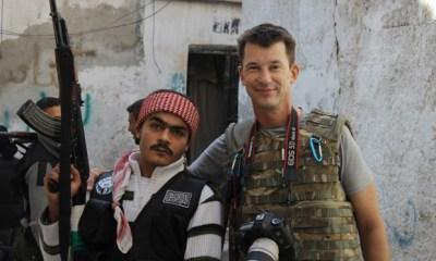 In this Nov. 11, 2012 photo, freelance British photojournalist John Cantlie poses with a Free Syrian Army rebel in Aleppo, Syria. The Islamic State group on Thursday, Sept. 18, 2014 released a video showing the British journalist who says he is a prisoner of the extremists. In a slick, three-minute video shot with three cameras, Cantlie, a photojournalist, said he worked for publications including The Sunday Times, The Sun and The Sunday Telegraph and came to Syria in November 2012 where he was subsequently captured by the Islamic State group.(AP Photo)