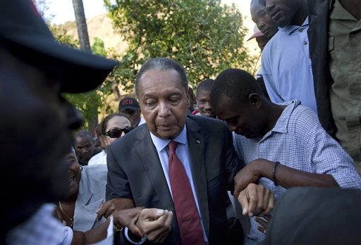 """In this Feb. 8, 2011 file photo, former Haitian dictator Jean-Claude """"Baby Doc"""" Duvalier's supporters help him negotiate an uneven path during a visit to his mother's hometown and grave site in Leogane, Haiti. (AP Photo/Ramon Espinosa, File)"""