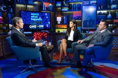 """In this image released by Bravo shows host Andy Cohen, left, speaks with Teresa Giudice, and her husband Joe Giudice, cast members on """"The Real Housewives of New Jersey,"""" during a taping of """"Watch What Happens Live,"""" airing Monday, Oct. 6, 2014 on Bravo. Teresa was sentenced to 15 months in prison on conspiracy and bankruptcy charges and Joe was sentenced to 41 months last Thursday in federal court in Newark, N.J. (AP Photo/Bravo, Charles Sykes)"""