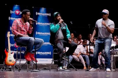 """Shawn Stockman, from left, Wanya Morris, and Nathan Morris of the musical group Boyz II Men, perform at their alma mater, Creative and Performing Arts High School, Tuesday, Oct. 14, 2014, in Philadelphia. The Grammy-winning R&B group, best known for '90s hits like """"I'll Make Love To You"""" and """"Motownphilly,"""" is set to release their new album, """"Collide,"""" next week. (AP Photo/Matt Rourke)"""