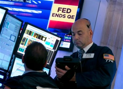 Trader Fred DeMarco, right, works on the floor of the New York Stock Exchange, as a television screen shows the decision of the Federal Reserve, Wednesday, Oct. 29, 2014.  The Fed plans to keep a key interest rate at a record low to support a U.S. job market that's improving but still isn't fully healthy and help lift inflation from unusually low levels. As expected, it's also ending a bond purchase program that was intended to keep long-term rates low. (AP Photo/Richard Drew)