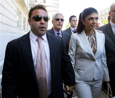 "In this July 30, 2013 file photo, ""The Real Housewives of New Jersey"" stars Giuseppe ""Joe"" Giudice, 43, left, and his wife, Teresa Giudice, 41, of Montville Township, N.J., walk out of Martin Luther King, Jr. Courthouse after an appearance in Newark, N.J. Teresa and Giuseppe ""Joe"" Giudice are scheduled to be sentenced Thursday Oct. 2, 2014 on conspiracy and bankruptcy fraud charges in federal court in Newark. (AP Photo/Julio Cortez, File)"