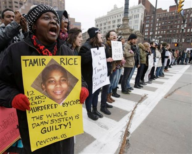 Demonstrators block Public Square Tuesday, Nov. 25, 2014, in Cleveland, during a protest over the weekend police shooting of Tamir Rice. The 12-year-old was fatally shot by a Cleveland police officer Saturday after he reportedly pulled a replica gun at the city park. (AP Photo/Tony Dejak)