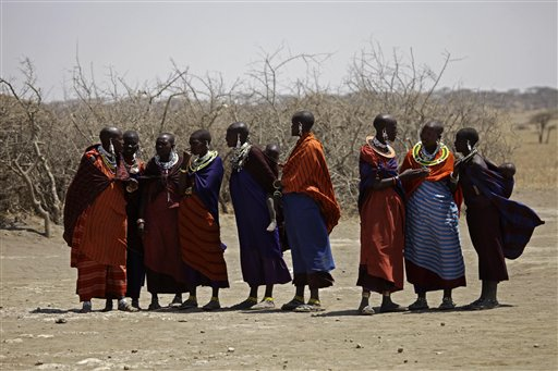 FILE - In this Monday, Aug. 12, 2013 file photo, Maasai tribeswomen gather at a village on the outskirts of the Serengeti, in northern Tanzania. A Maasai community near Tanzania's Serengeti National Park looks likely to keep their traditional homeland after the country's president Jakaya Kikwete said on Twitter on Sunday, Nov. 23, 2014 that the government would not take their land. (AP Photo/Nariman El-Mofty, File)