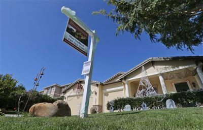 In this Oct. 27, 2014 photo, a realty sign is posted in front of a home for sale in Carlsbad, Calif. Real estate date provider CoreLogic releases its September report on U.S. home prices on Tuesday, Nov. 4, 2014. (AP Photo/Lenny Ignelzi)