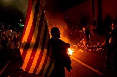 James Cartmill holds an American flag while protesting in Oakland, Calif., on Monday, Nov. 24, 2014, after the announcement that a grand jury decided not to indict Ferguson police officer Darren Wilson in the fatal shooting of Michael Brown, an unarmed 18-year-old. Several thousand protesters marched through Oakland with some shutting down freeways, looting, burning garbage and smashing windows. (AP Photo/Noah Berger)