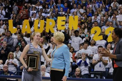 Mount St. Joseph's Lauren Hill, left, smiles at Pat Summit after receiving the Pat Summitt Award during halftime of her first NCAA college basketball game against Hiram University at Xavier University in Cincinnati on Sunday, Nov. 2, 2014. The NCAA allowed Mount St. Joseph's season opener to be moved up to Nov. 2, so that Hill, who has an inoperable brain tumor, to be able to play in a college basketball game. WNBA Player Tamika Devonne Catchings, of the Indiana Fever is at the right. (AP Photo/Tom Uhlman)