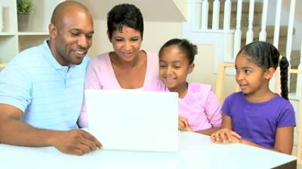 stock-footage-young-african-american-family-using-a-laptop-to-talk-with-family-and-friends-via-internet-web-chat