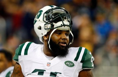 In this Nov. 24, 2014, file photo, New York Jets defensive end Sheldon Richardson watches during warmups before an NFL football game against the Buffalo Bills in Detroit. Richardson felt helpless as he watched the scenes near his hometown unfold on TV and social media. He was born and raised in St. Louis, just a few minutes away from the suburb of Ferguson, Mo., where police officer Darren Wilson was not indicted by a grand jury last week in the shooting death of Michael Brown. (AP Photo/Paul Sancya, File)