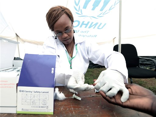 In this photo taken Sunday, Nov. 30, 2014, a medical personal administers an AIDS test in Gambella, Ethiopia, More than 3,300 people were tested for HIV Sunday in the Ethiopian region of Gambella, a massive turnout that exceeded expectations among AIDS campaigners who had hoped to test 2,000 people, according to local officials. She said 3,383 people were tested for HIV within eight hours in a single event ahead of World Aids Day. Eighty-two of them received positive results. (AP Photo)